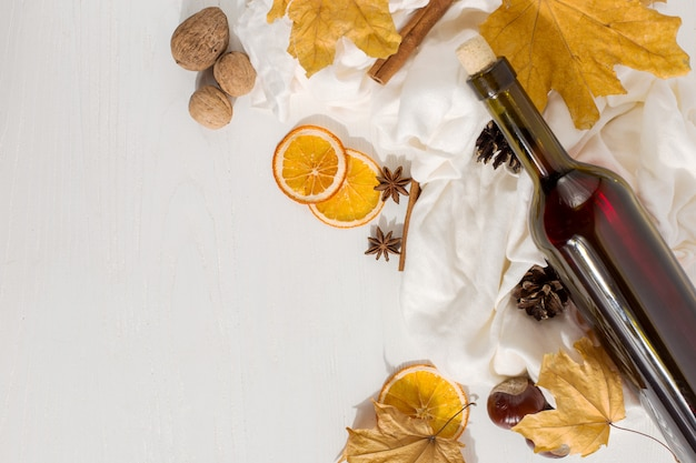 Mulled wine with spices, bottle, scarf, spices, dry leaves and oranges on the table. autumn mood, method to keep warm in cold, copyspace.