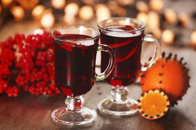 Mulled wine with spices and christmas tree on wooden background