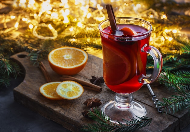 Mulled wine with spices and christmas tree on wooden surface