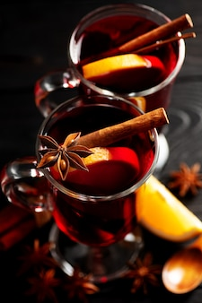 Mulled wine with spices poured into glass glasses on a wooden dark surface