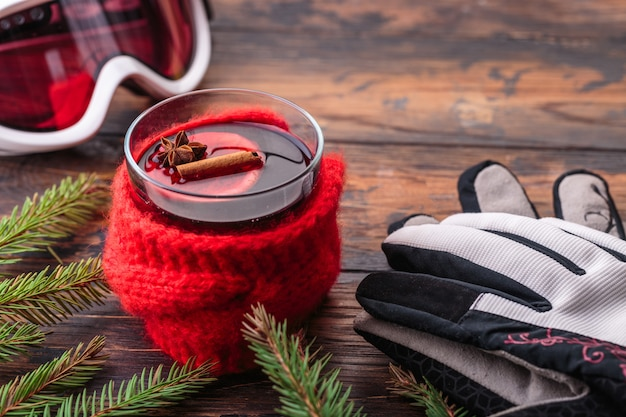 Mulled wine in woman hands cozy home concept ingredients winter sport goggles ski gloves