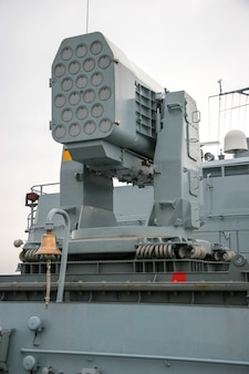 Multi-barrel missile launcher on a ship. many gun barrels. an interesting system of depreciation from steel cables. near the ship's bell.