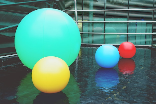 Multi color balls on the water pool. background