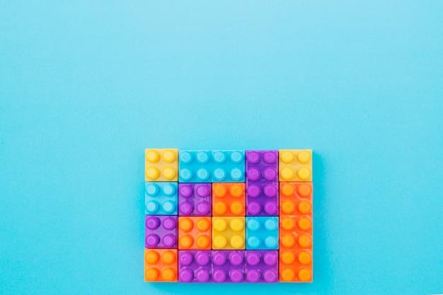 Multi-color toy bricks on blue background
