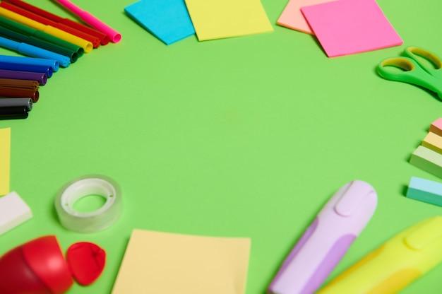 Разноцветный ассортимент канцелярских принадлежностей и школьных принадлежностей, расположенных по кругу на светло-зеленом фоне, копировальное пространство