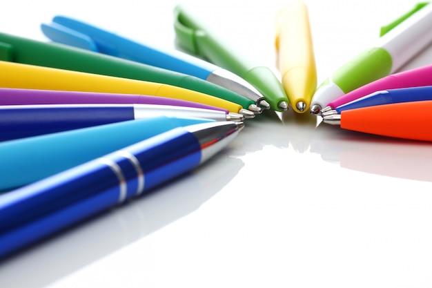 Разноцветные шариковые ручки на белом фоне