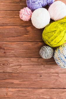 Multi colored ball of yarns on wooden background