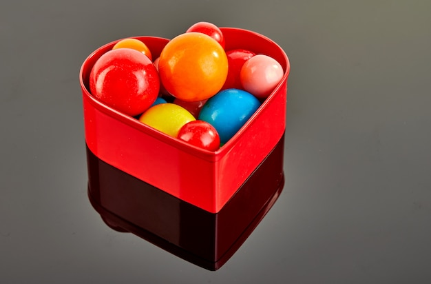 Multi colored balls of chewing gum on a gray background in a red heart with reflection.