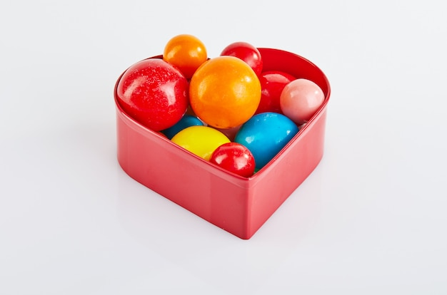 Multi colored balls of chewing gum on a white background in a red heart with reflection.