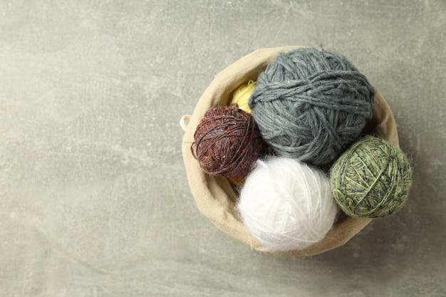 Разноцветные шарики пряжи в плетеной корзине на светло-сером фоне.