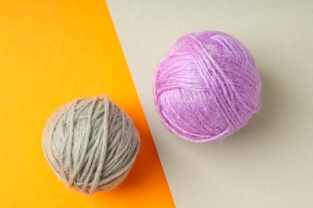 Разноцветные шарики пряжи на двухцветном фоне.