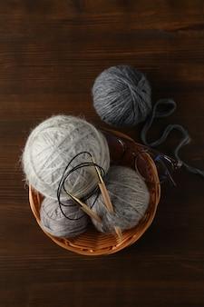 Разноцветные шарики пряжи спицами в плетеной корзине на деревянном фоне.