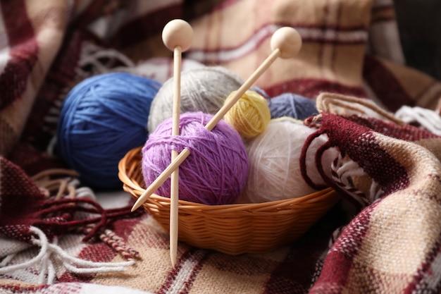 格子縞の背景に籐のバスケットに編み針と糸のマルチカラーボール。