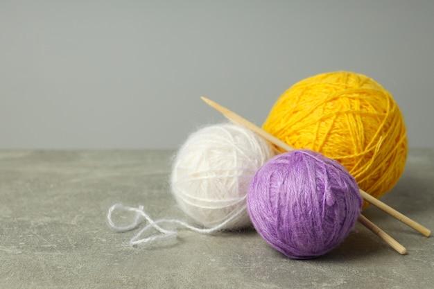 Разноцветные шарики пряжи спицами на светло-сером фоне.