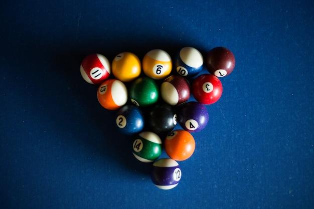 青いテーブルの上のマルチカラーのビリヤードボール