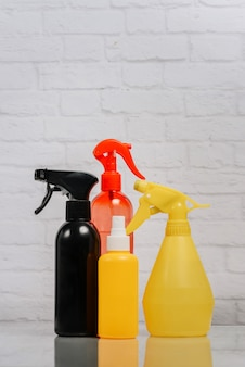 Multi-colored bottles with cleaning products on a wall of a white brick wall.