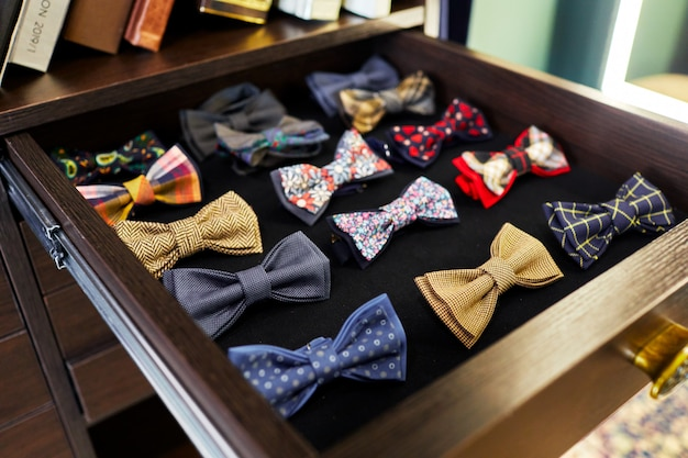 Multi-colored bow tie lying in wooden shelf with black lining