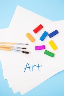 マルチカラーの明るい絵の具、さまざまなサイズの水彩ブラシは、青い背景の水彩紙の上に一緒に横たわっています。閉じる。碑文は芸術です。
