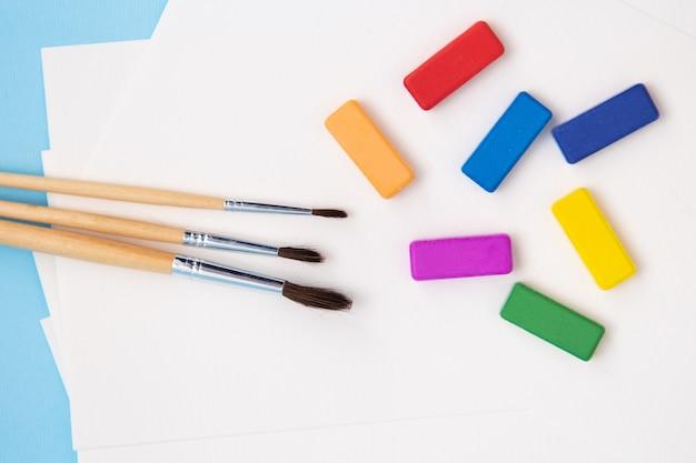 Разноцветные яркие краски, акварельные кисти разного размера лежат вместе на акварельной бумаге на синем фоне. крупный план.