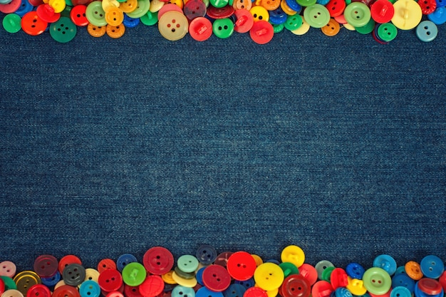 Multi colored buttons to the side of a denim fabric background
