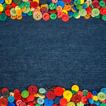 Multi colored buttons to the side of a denim fabric background Premium Photo