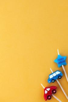 텍스트에 대 한 공간을 가진 노란색 표면에 멀티 컬러 촛불 자동차