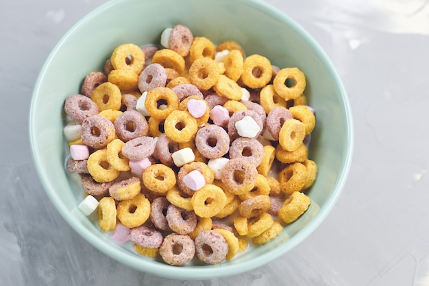 Multi colored cereal fruit loops in a bowl on gray background close up copy space breakfast concept