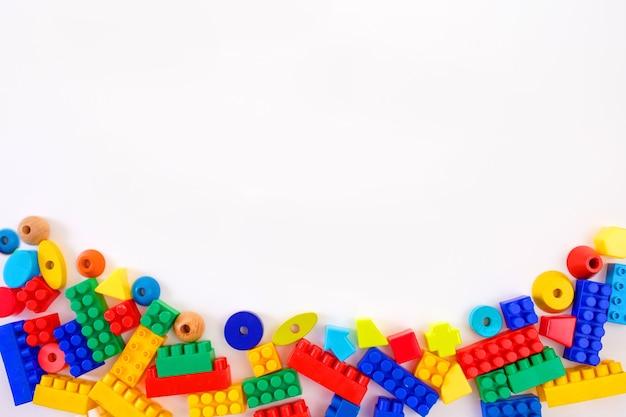 白い背景の上面図にマルチカラーの子供のおもちゃのコンストラクター。テキスト用のスペース