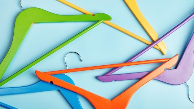 Разноцветные вешалки на синем столе