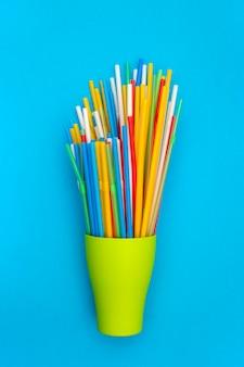 Разноцветные коктейльные трубки в зеленой чашке на синем фоне