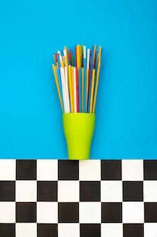 Разноцветные коктейльные трубочки в зеленой чашке