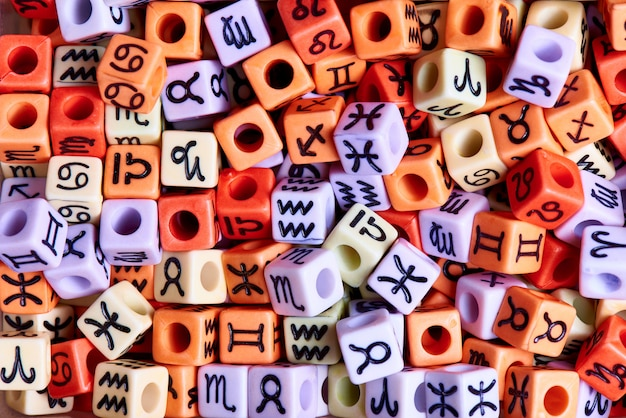 Multi-colored cubes with zodiac signs close-up.