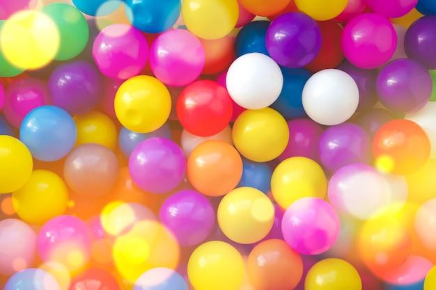 マルチカラーのデザイナーの背景。子供の遊び場で楽しくジャンプするための多くのカラフルなボール。閉じる。子供の休日の背景。子供の誕生日。