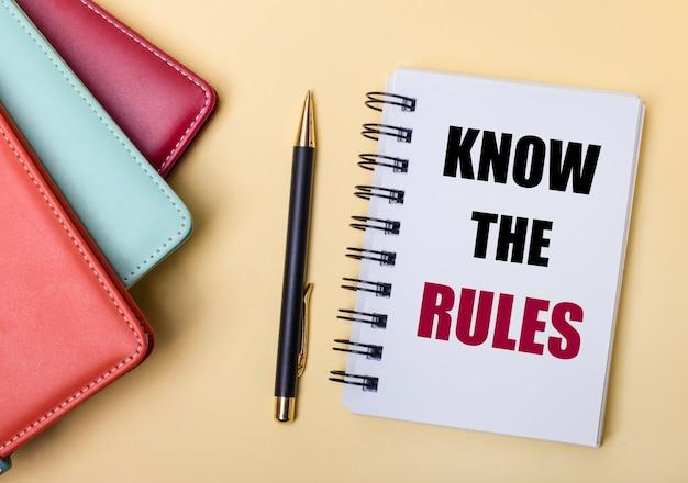 여러 가지 색의 일기가 베이지 색 배경 위에 놓여 있으며, 펜과 노트 옆에는 규칙을 알고 계십시오. 평평하다.