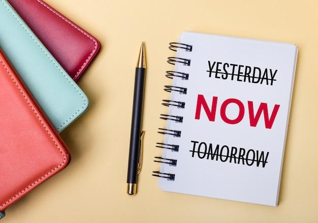 여러 가지 색의 일기가 yesterday now tomorrow라는 단어가 적힌 펜과 노트 옆에 베이지 색 배경에 놓여 있습니다. 평평하다.