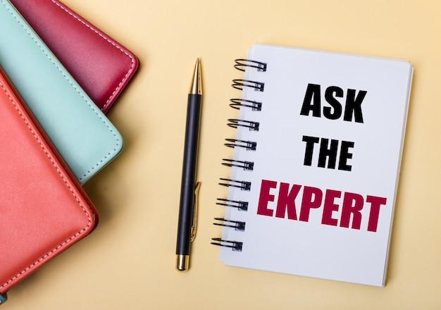 マルチカラーの日記は、ペンとノートの横にあるベージュの表面に、ask theexpertという言葉が書かれています。フラットレイ。