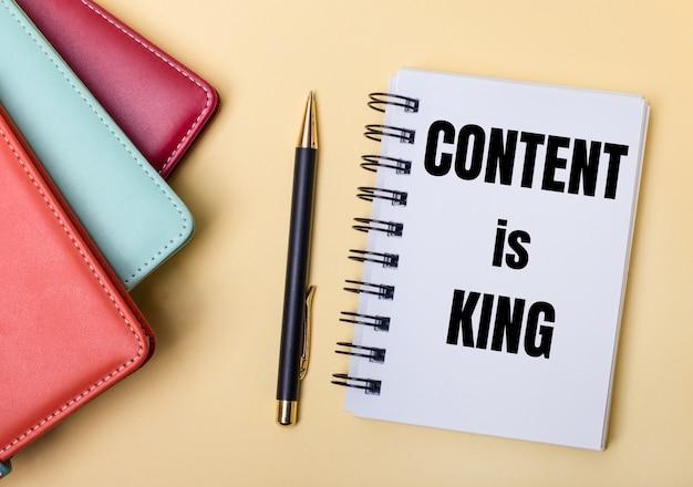 여러 가지 색상의 일기는 content is king이라는 단어가 적힌 펜과 노트북 옆의 베이지 색 표면에 놓여 있습니다. 플랫 레이