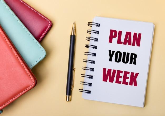 여러 가지 색의 일기는 plan your week라는 단어가 적힌 펜과 노트북 옆의 베이지 색 벽에 놓여 있습니다. 평평하다.