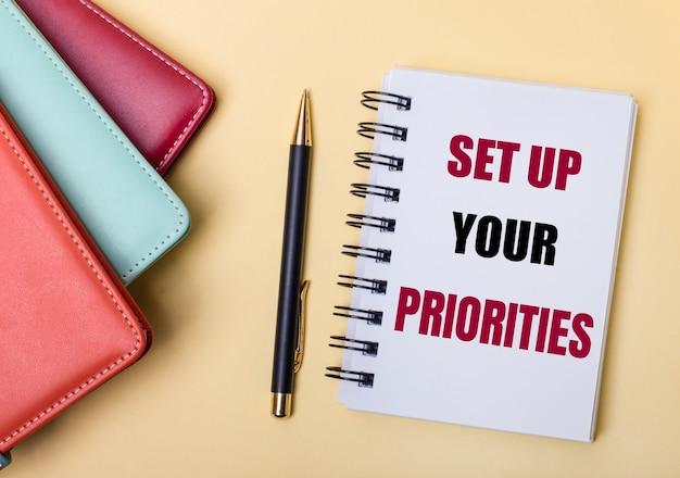 Разноцветные дневники лежат на бежевой стене рядом с ручкой и блокнотом с надписью устанавливайте приоритеты. плоская планировка.