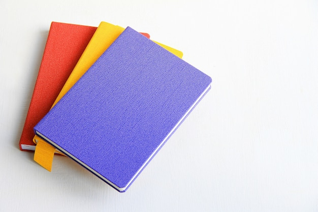 Multi-colored diaries on a light wooden background, red, blue, yellow notepads
