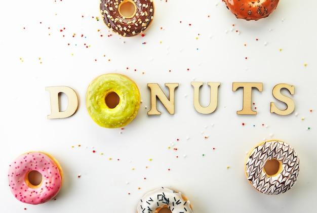 Разноцветные пончики с глазурью, брызгами и пончиками надписи на белом фоне. плоская планировка