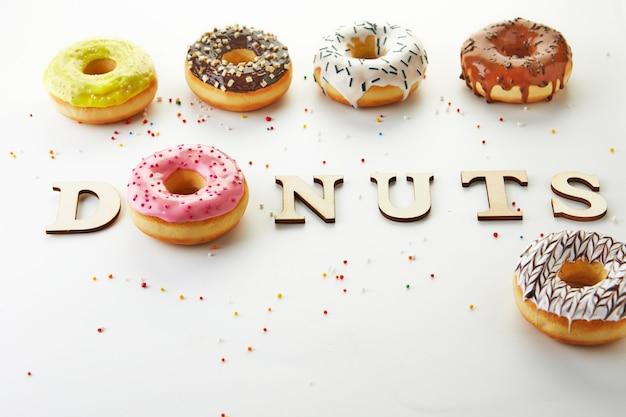 白い背景にアイシング、スプリンクル、碑文ドーナツとマルチカラードーナツ。