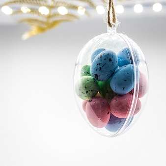 Multi-colored easter eggs hang in glass transparent egg bauble