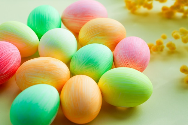 黄色の背景にパステルトーンのマルチカラーの卵。イースター装飾