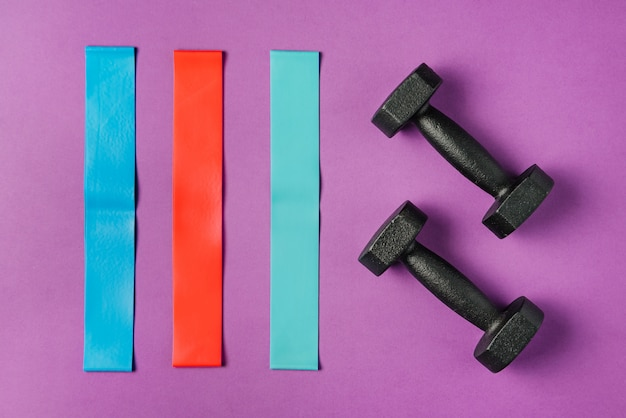 Multi-colored elastic bands for fitness and two dumbbells on a colored wall.