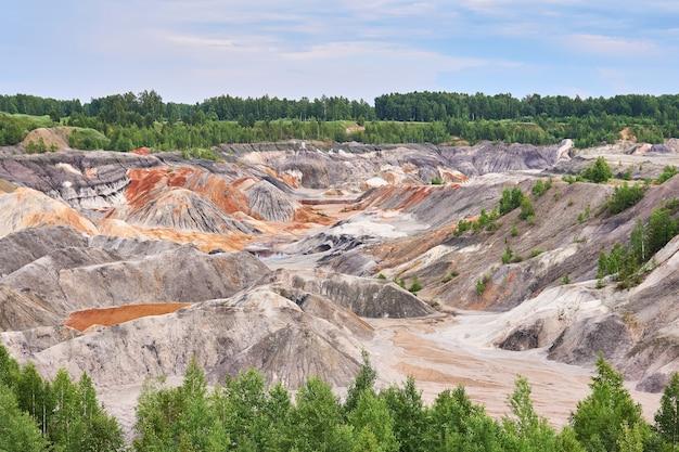 카올린의 노천 채굴 현장에서 다양한 색상의 침식된 언덕과 파괴된 토양층