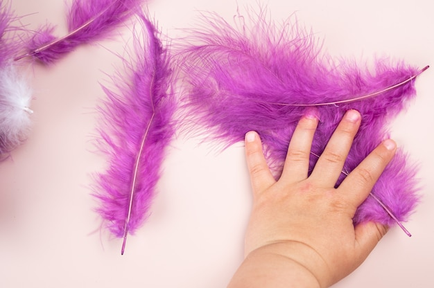 子供の手にあるマルチカラーの羽。