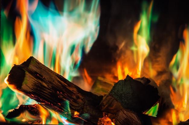 マルチカラーの火の炎が暖炉で燃える