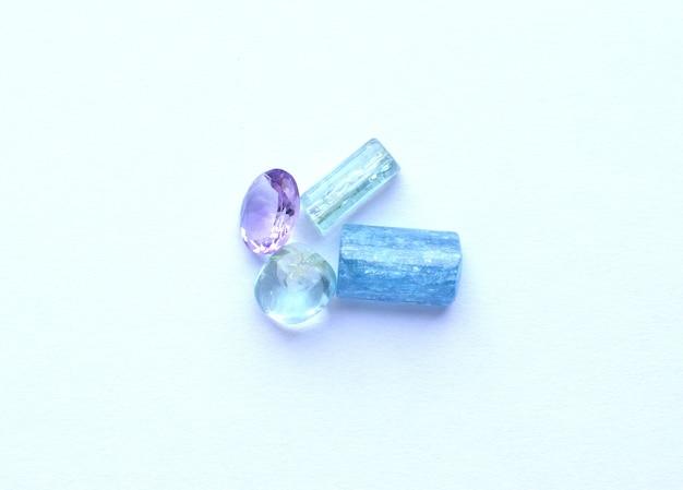 Разноцветные драгоценные камни, топаз, кристаллы аквамарина и аметиста.