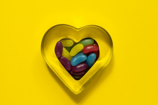 Multi-colored glazed jelly beans sweets in heart cookies mold on yellow background with copy space.
